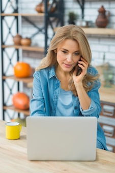 Smiling portrait of a blonde young woman using laptop while talking on mobile phone