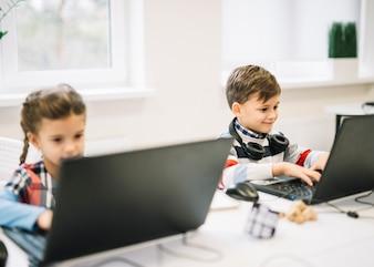 教室で女の子と座っているラップトップを使用して男の子の肖像画を笑顔