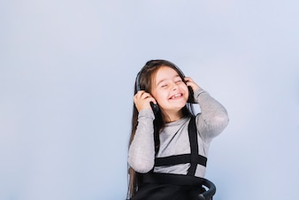 Smiling portrait of a girl enjoying the music on headphone against blue background