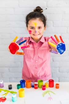 Улыбающийся портрет девушки, показывая ее окрашенные красочные руки