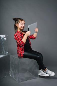Smiling portrait of a girl sitting on translucent block looking at digital tablet