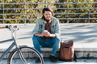 Smiling portrait of a man sitting on sidewalk with his backpack holding disposable coffee cup