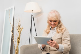 Smiling portrait of a senior woman sitting on sofa looking at digital tablet