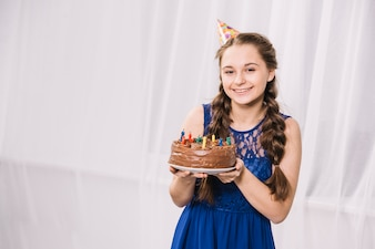 Smiling portrait of a teenage girl holding birthday cake decorated with colorful balloons