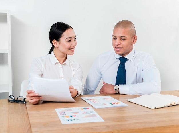 Усмехаясь портрет молодого бизнесмена и коммерсантки обсуждая отчет на рабочем месте