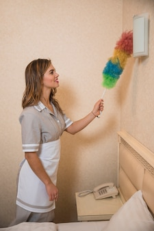 Smiling portrait of a young maid cleaning the wall light with colorful soft duster