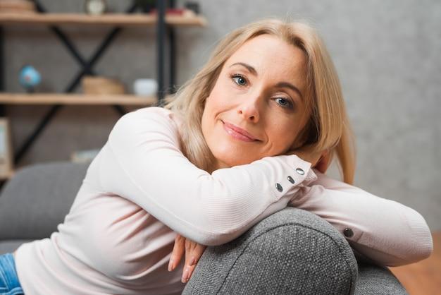 Улыбается портрет молодой женщины, опираясь на серый диван