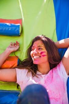 Улыбающийся портрет молодой женщины с цветом холи на ее лице, глядя в сторону