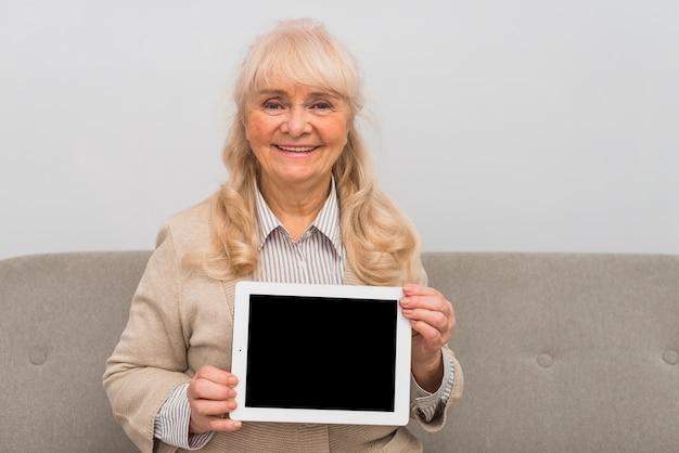 空白の画面を持つデジタルタブレットを示す金髪の年配の女性の肖像画を笑顔