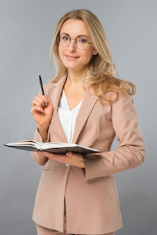 Smiling portrait of blonde young woman holding pen and diary in hand against gray background