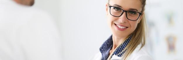 近くに眼鏡をかけた女性医師の笑顔の肖像画。医療と診断の概念