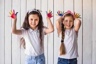 Усмехаясь портрет 2 девушек показывая красочные покрашенные руки стоя против деревянной стены