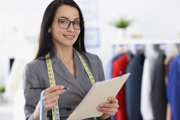 Улыбающийся портрет женщины-дизайнера в ателье. швейные услуги по пошиву одежды concept