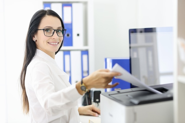 Smiling portrait of secretary who is holding papers next to the printer.