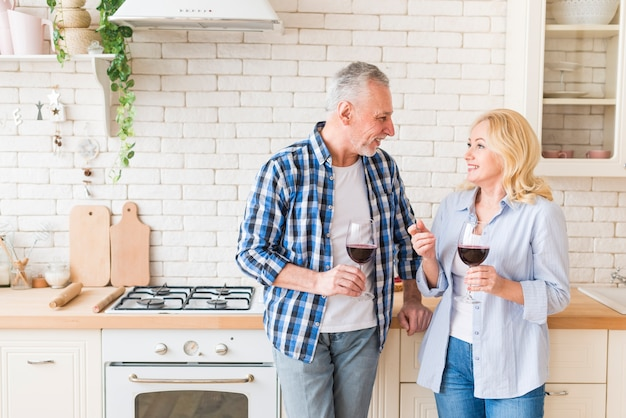 Smiling portrait of a senior young couple looking at each other holding wineglass in hand