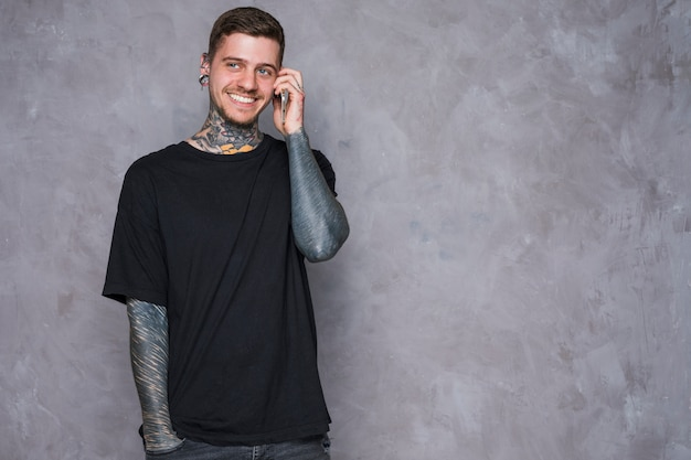 Smiling portrait of a tattooed young man with pierced ears talking on mobile phone