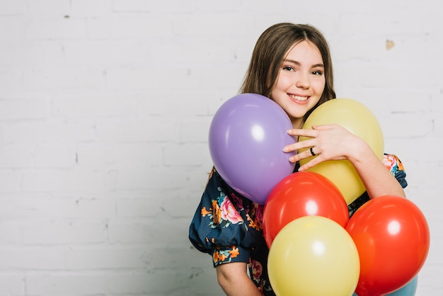 Smiling portrait of a teenage girl holding balloons