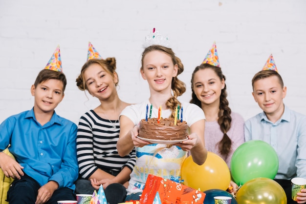 Smiling portrait of a teenage girl sitting with her friends holding birthday cake