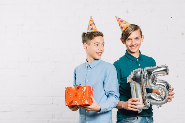 Smiling portrait of two boys wearing party hat on head holding gift box and number 15 foil balloon