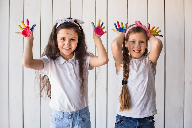 Smiling portrait of two girls showing colorful painted hands standing against wooden wall