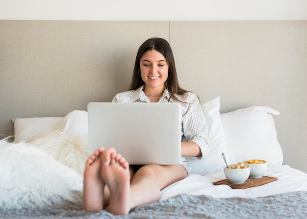 Smiling portrait of a woman sitting on bed with healthy breakfast using laptop