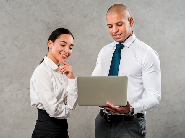 Smiling portrait of a young businessman and businesswoman looking at laptop
