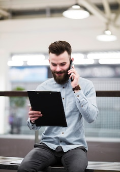 Smiling portrait of a young businessman looking at clipboard talking on mobile phone