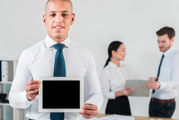 Smiling portrait of young businessman showing blank screen digital tablet against colleague at backdrop