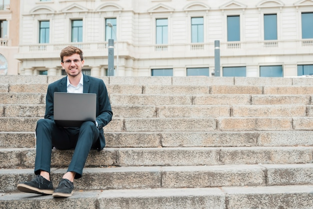 Smiling portrait of a young businessman sitting on staircase using digital tablet