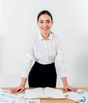 Smiling portrait of a young businesswoman standing behind the desk against white wall