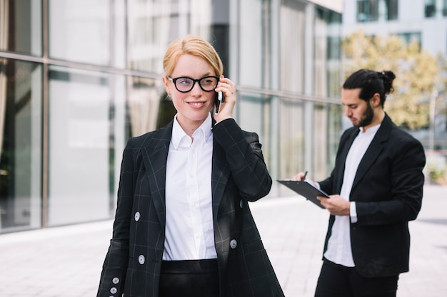 Smiling portrait of a young businesswoman talking on cell phone with man writing on clipboard at background