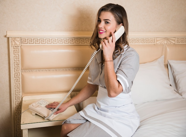 Smiling portrait of a young chambermaid speaking on room telephone