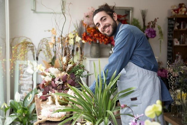 Smiling portrait of a young man arranging the flower in the florist shop