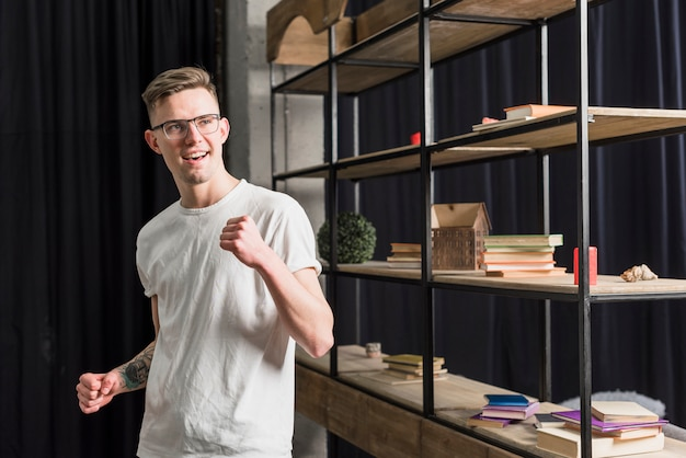 Smiling portrait of a young man clenching his fist standing near the shelf