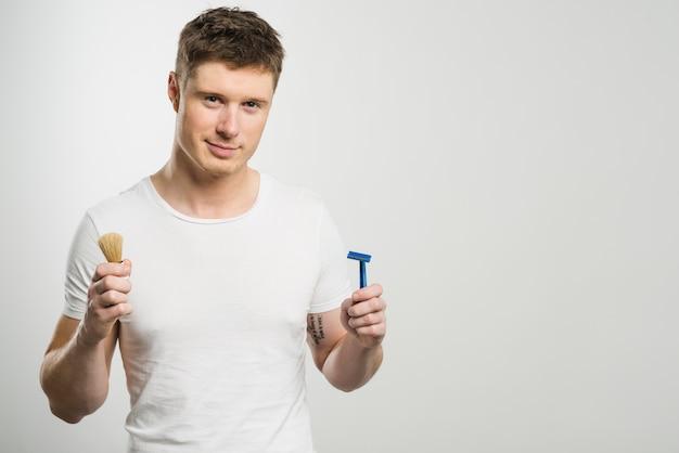 Smiling portrait of a young man holding razor and shaving brush in hands