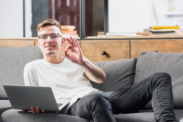 Smiling portrait of a young man lying on sofa holding laptop in hand showing ok sign