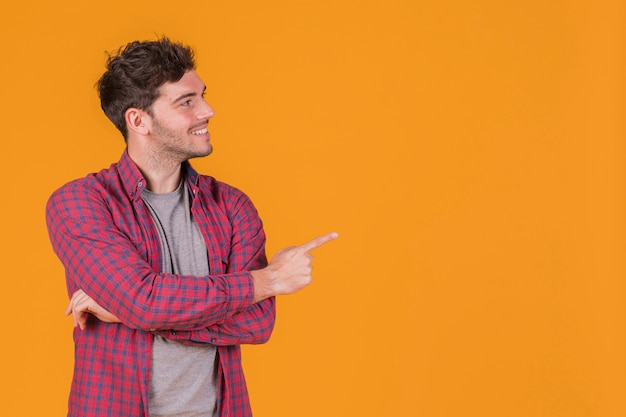 Smiling portrait of a young man pointing his finger against an orange backdrop