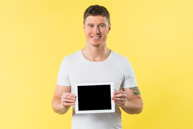 Smiling portrait of a young man showing digital tablet against yellow backdrop