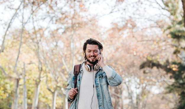 Smiling portrait of a young man walking with his backpack talking on cell phone in the park