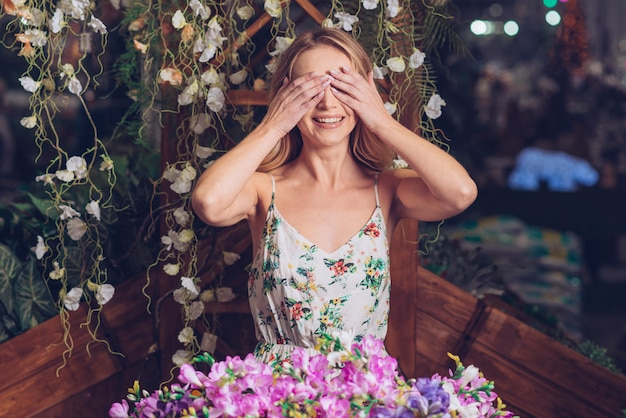 Smiling portrait of a young woman covering her eyes with two hands standing in front of flowers