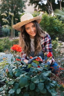 Smiling portrait of a young woman cutting the beautiful grown up rose with shears