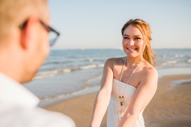 Smiling portrait of a young woman enjoying with his boyfriend at beach