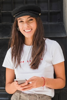 Smiling portrait of a young woman holding mobile phone in hand looking at camera