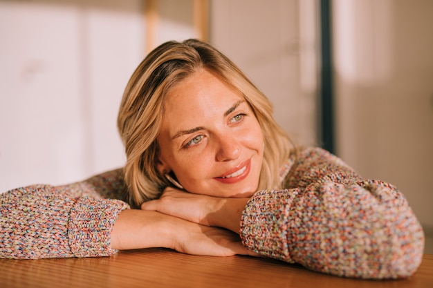 Smiling portrait of a young woman leaning on wooden desk daydreaming