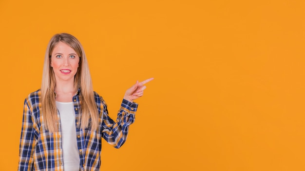Smiling portrait of a young woman pointing her finger at something on orange background