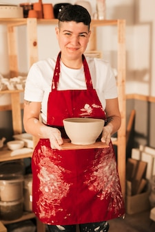 Smiling portrait of a young woman in red apron holding handmade clay bowl on wooden tray