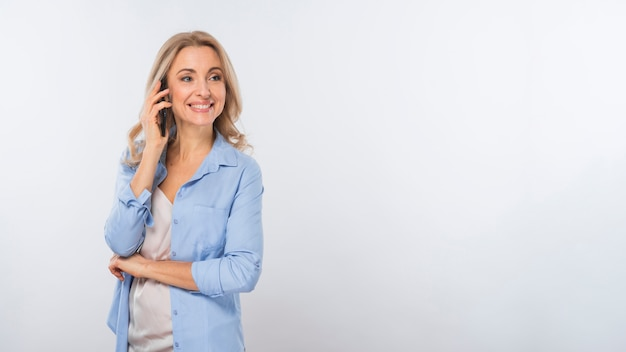 Smiling portrait of a young woman talking on mobile phone standing against white background