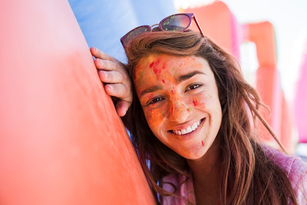 Smiling portrait of a young woman with holi colors on face powder looking at camera
