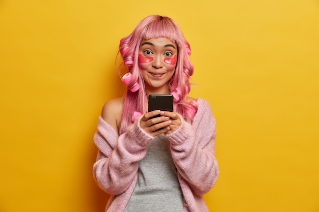 Smiling positive asian woman holds mobile phone in hands, checks email box, looks gladfully, has pink hair, wears rollers
