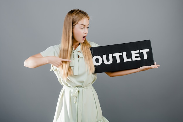 Smiling positive blonde woman with outlet sign isolated over grey